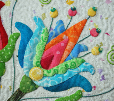 "The triple threat of machine quilting: Beads, embroidery and applique.  Just remember to background fill up to the edge, outline and fill if necessary.  Also remember you have the option of raising your presser foot to avoid ""catching"" your elements and pulling."